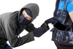 Il ladro ruba il telefono della giovane donna sullo studio immagine stock libera da diritti