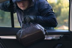 Il ladro ruba una borsa dall'automobile attraverso il vetro aperto immagini stock