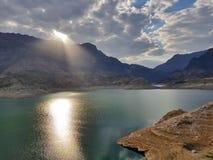 Il lago blu nelle montagne con il sole riflette nell'acqua fotografie stock