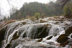 Il lago e la cascata in montagna Fotografie Stock
