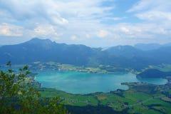 Il lago ha chiamato Wolfgangsee in Austria con le montagne nei precedenti e le nuvole sul cielo e sull'erba nella parte anteriore Immagini Stock