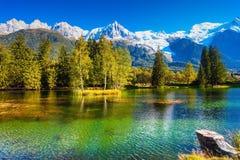 Il lago ha riflesso le alpi innevate Fotografia Stock