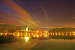 Il lago ha sanguinato, isola sanguinata e presupposto di vergine Maria, Slovenia - vista della chiesa di notte Immagine Stock