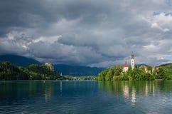 Il lago ha sanguinato, vista del castello e chiesa in tempo tempestoso con il sole dopo pioggia Immagini Stock