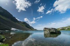 Il lago mountain con il grande masso e un resto si fermano su una strada del passo di montagna vicino a Tavate nelle alpi svizzer Fotografia Stock