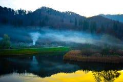 Il lago nel distretto di Noua di Brasov Romania ed il fumo del barbecue Immagine variopinta di tramonto fotografia stock