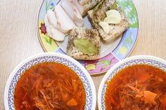 Il lardo salato con pepe, la foglia di alloro e le bugie dell'aglio su un piatto, accanto là è due piatti con borsch rosso Primo  immagine stock