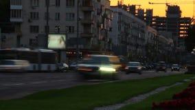 Il lasso di tempo del traffico cittadino al crepuscolo, luci delle automobili passa vicino, ottiene il buio archivi video