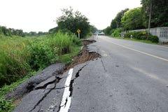 Il lato della strada asfaltata rotta è sprofondato e caduto dopo l'inondazione Immagine Stock Libera da Diritti