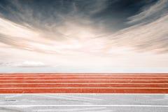 Il lato di angolo basso ha sparato di una pista corrente, arancio Fotografia Stock