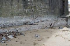 Il lato di vecchia costruzione concreta ha danneggiato dall'oceano Immagine Stock