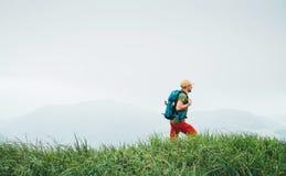 Il lato ha sparato dell'uomo della viandante che cammina dal percorso nuvoloso nebbioso della catena montuosa del tempo con lo za fotografia stock libera da diritti