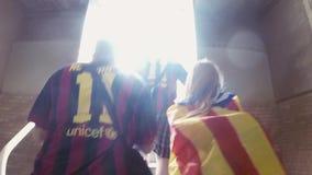 Il lato posteriore dell'uomo e la ragazza camminano sulle scale su stadio di football americano in camicia del fan in Spagna Gior archivi video