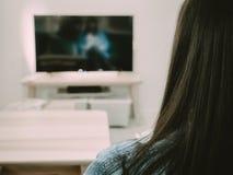 Il lato posteriore della donna dei capelli neri si siede, si rilassa e guarda la TV nel suo liv fotografie stock libere da diritti