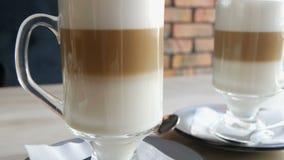 Il latte del caffè con latte e l'aria spumano e una paglia nera sta in un vetro speciale trasparente sulla tavola in caffè alla m archivi video