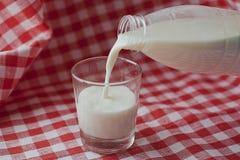 Il latte naturale è versato da una bottiglia in un vetro Fotografia Stock