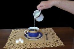 Il latte sta versando da una brocca di latte diritto in una tazza di caffè fotografie stock libere da diritti