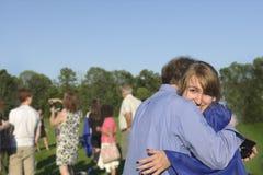 Il laureato abbraccia il suo papà dopo l'inizio Immagini Stock