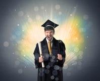 Il laureato felice con bokeg variopinto si accende nei precedenti fotografia stock libera da diritti