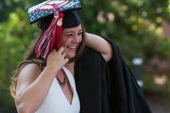 Il laureato femminile sorridente prepara mettere sopra l'abito di graduazione Immagine Stock