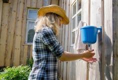 Il lavaggio della donna dell'agricoltore passa lo strumento di plastica rurale della rondella Immagine Stock Libera da Diritti