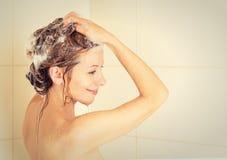 Il lavaggio sorridente della donna si dirige con sciampo in una doccia Fotografie Stock