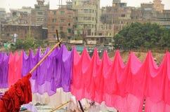 Il lavaggio variopinto sta appendendo al fiume in Dacca Fotografia Stock