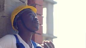 Il lavoratore afroamericano della costruzione prende una rottura che mangia un panino stock footage