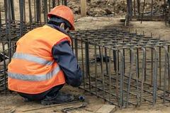 Il lavoratore al cantiere fa la carcassa del tondo per cemento armato immagine stock