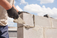 Il lavoratore allinea con una spatola, blocchetti di cenere del mattone di disposizione Fotografie Stock