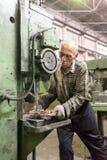 Il lavoratore anziano perfora i fori sul dettaglio dalla perforatrice Immagine Stock