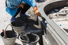Il lavoratore applica il cemento sopra la superficie del bordo del sentiero per pedoni Immagini Stock Libere da Diritti