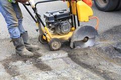 Il lavoratore avvia il motore della taglierina della benzina per tagliare e rimuovere il cattivo asfalto sulla carreggiata fotografia stock