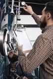 Il lavoratore barbuto della fabbrica di birra annota le letture dal fare l'attrezzatura fermentazione brewery Elaborazione della  fotografia stock