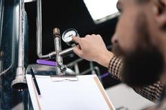Il lavoratore barbuto della fabbrica di birra annota le letture dal fare l'attrezzatura fermentazione brewery Elaborazione della  immagine stock libera da diritti