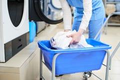 Il lavoratore carica l'abbigliamento della lavanderia nella lavatrice Fotografia Stock
