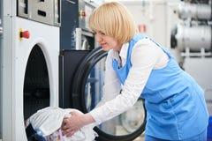 Il lavoratore carica l'abbigliamento della lavanderia nella lavatrice Immagini Stock Libere da Diritti