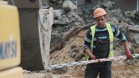 Il lavoratore in casco ha messo il righello industriale lungo sotto l'escavatore al cantiere archivi video