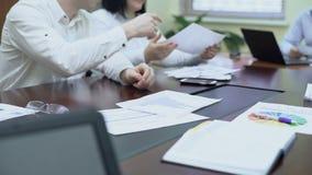 Il lavoratore che passa il diagramma ai colleghi alla riunione corporativa, buona società risulta stock footage