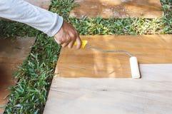 Il lavoratore che per mezzo del rullo applica il sigillatore sull'arenaria immagini stock