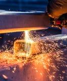 Il lavoratore che taglia il tubo d'acciaio facendo uso della torcia del metallo ed installa il bordo della strada immagine stock