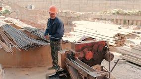 Il lavoratore che taglia perno lungo con una macchina speciale stock footage
