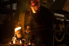 Il lavoratore cola il metallo fuso dalla siviera nello stampo fotografia stock libera da diritti