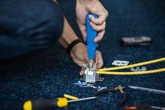 Il lavoratore collega un cavo della rete con gli incavi RJ45 dallo strumento della perforazione-giù, processo di stenditura della immagini stock libere da diritti