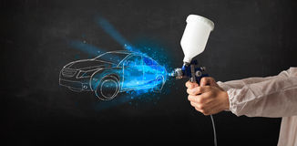 Il lavoratore con l'automobile disegnata a mano di verniciatura della pistola dell'aerografo allinea Fotografia Stock Libera da Diritti