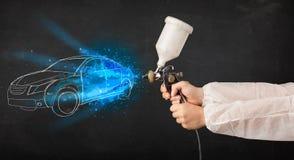 Il lavoratore con l'automobile disegnata a mano di verniciatura della pistola dell'aerografo allinea Fotografia Stock