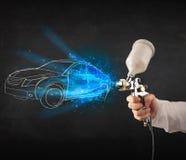 Il lavoratore con l'automobile disegnata a mano di verniciatura della pistola dell'aerografo allinea Immagine Stock