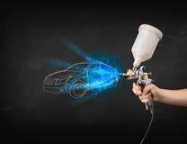 Il lavoratore con l'automobile disegnata a mano di verniciatura della pistola dell'aerografo allinea Immagini Stock Libere da Diritti