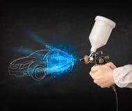 Il lavoratore con l'automobile disegnata a mano di verniciatura della pistola dell'aerografo allinea Fotografie Stock