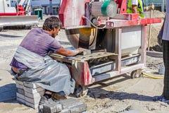 Il lavoratore con la sega circolare della lama del diamante sta tagliando pavimenta il bri di pietra Immagine Stock Libera da Diritti